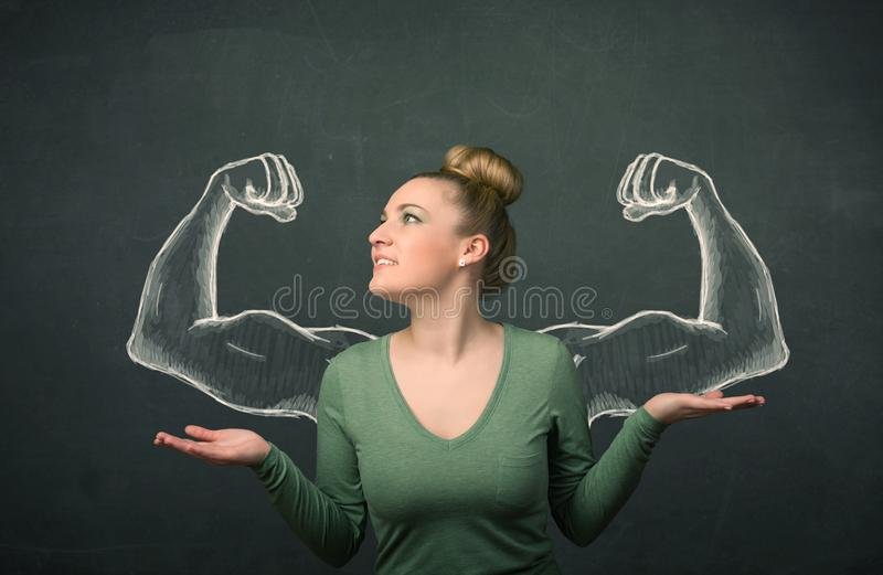 Woman with sketched strong and muscled arms. Pretty young woman with sketched strong and muscled arms royalty free stock photo