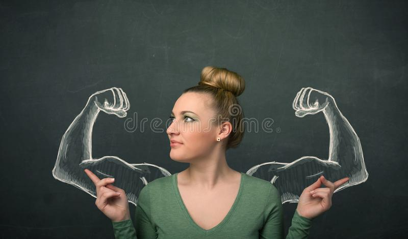 Woman with sketched strong and muscled arms. Pretty young woman with sketched strong and muscled arms royalty free stock images