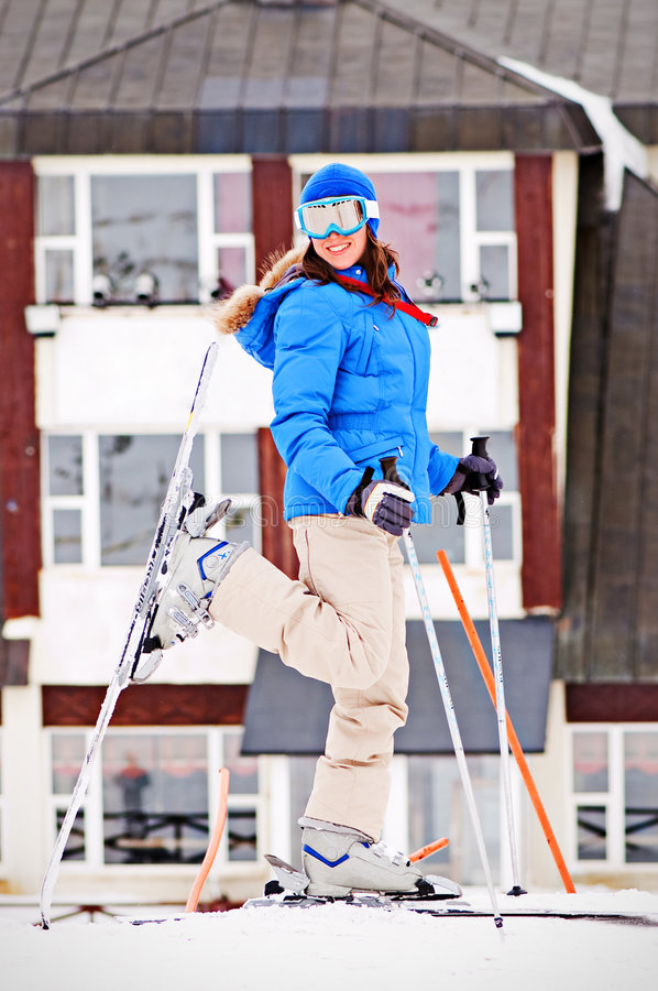 Woman in ski with hotel at the background royalty free stock photography