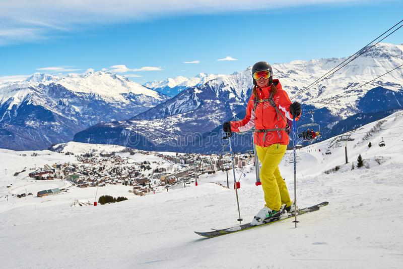 Woman skier posing on the ski slopes above La Toussuire village in France, Les Sybelles ski domain, on a perfect sunny day. Les Sybelles, France - March 12, 2019 royalty free stock photos