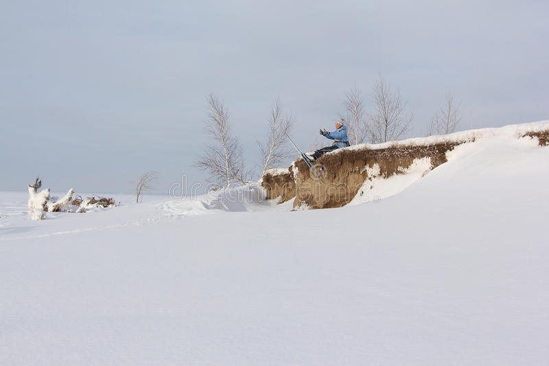 The woman the skier sitting on the bank of the river stock image
