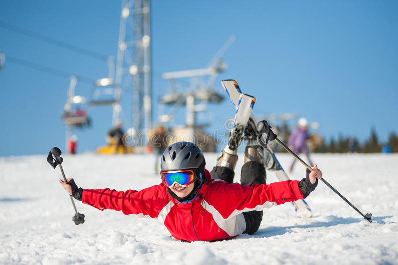 Woman skier with ski at winer resort in sunny day. Skier female in ski goggles lying with raised arms on snowy slope at mountain top in sunny day with ski lifts royalty free stock photography