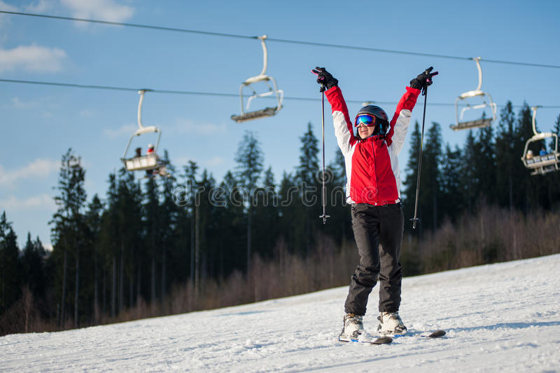 Woman skier with ski at winer resort in sunny day. Female skier wearing helmet, red jacket and ski goggles standing on snowy slope with hands raised up in sunny stock photo