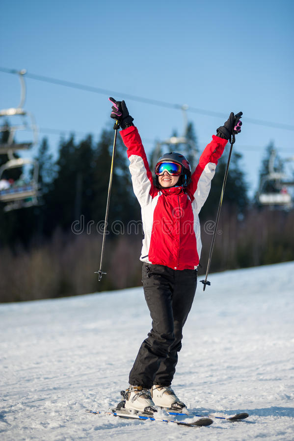 Woman skier with ski at winer resort in sunny day. Portrait of female skier wearing helmet, red jacket and ski goggles standing on snowy slope with hands raised stock photography
