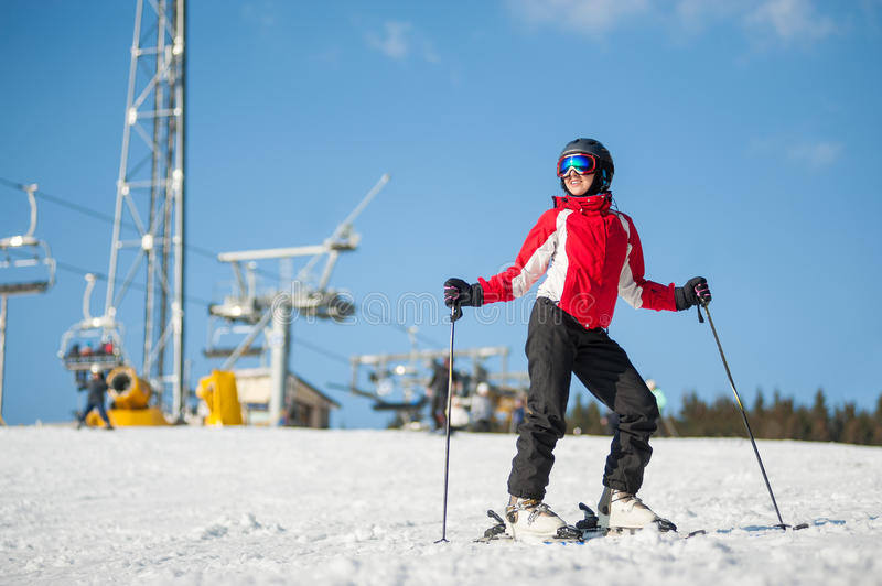 Woman skier with ski at winer resort in sunny day. Woman wearing helmet, red jacket and ski goggles standing with skis on mountain top at a winter resort in royalty free stock image