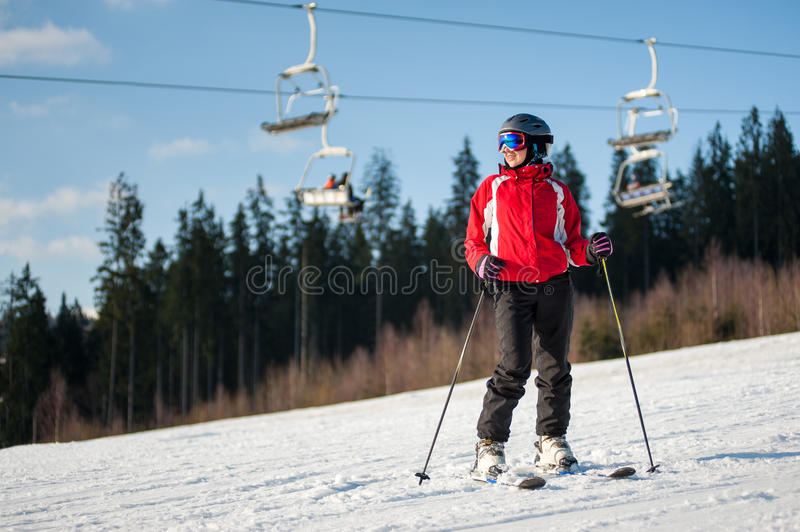 Woman skier with ski at winer resort in sunny day. Woman skier wearing helmet, red jacket and ski goggles standing with skis on snowy slope and looking away in stock images