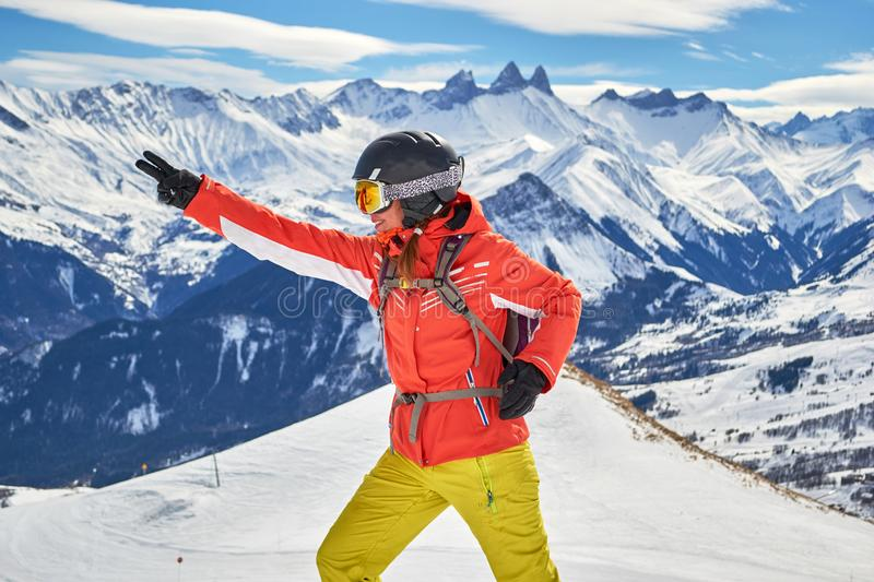 Woman skier smiling and posing at Les Sybelles ski domain, with Aiguilles d`Arves peaks in the background, on a sunny day. Woman skier smiling and posing at Les stock images