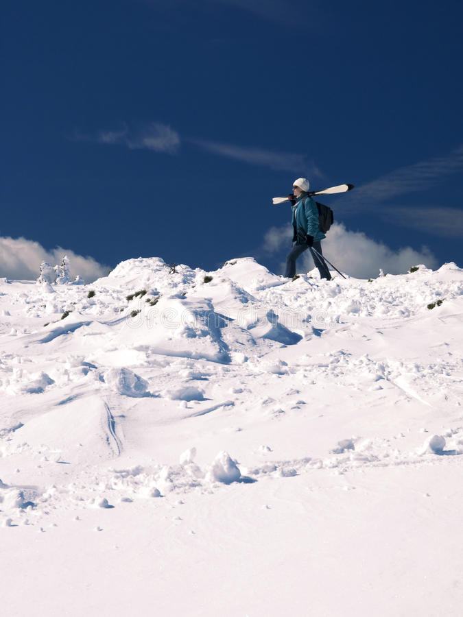 Woman skiing in the mountains. Girl walking in the mountain snow royalty free stock images