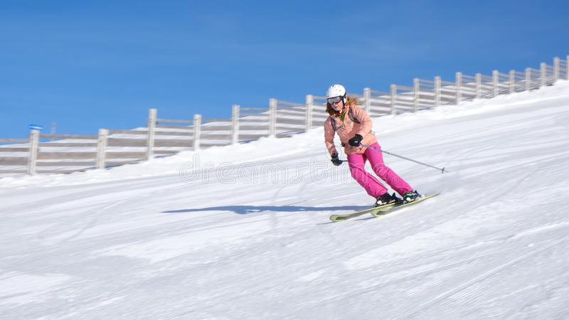 Woman skiing at Sinaia resort in Romania on a sunny day with perfect snow, on a medium difficulty slope red piste. stock photography