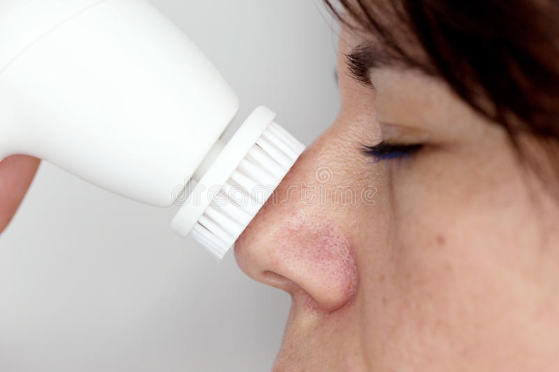 Woman with skin cleaning device stock image