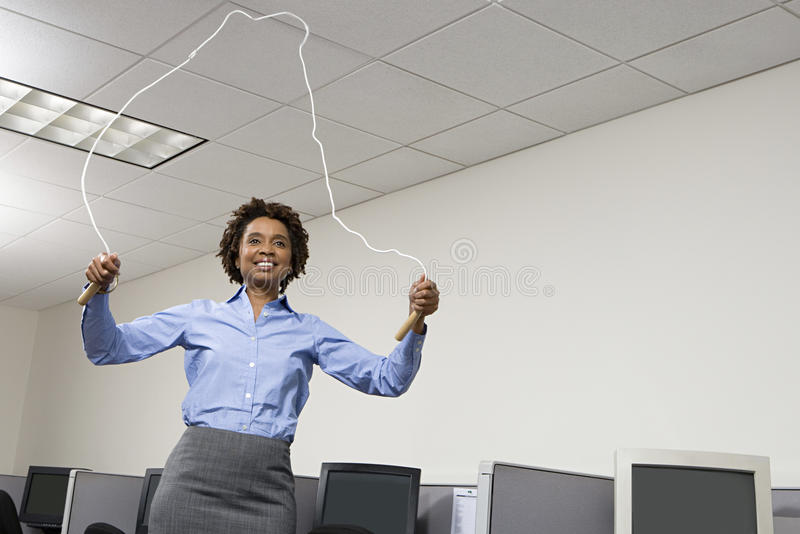 Woman skipping in office royalty free stock photography