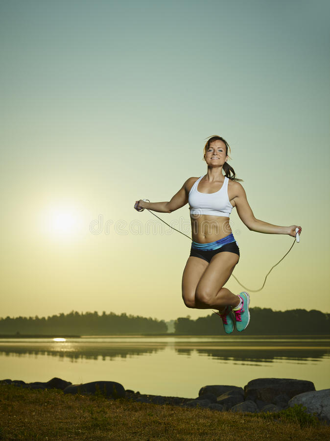 Woman and skipping rope. Young fitness woman used a skipping rope, sun and sea on background, copy space stock image