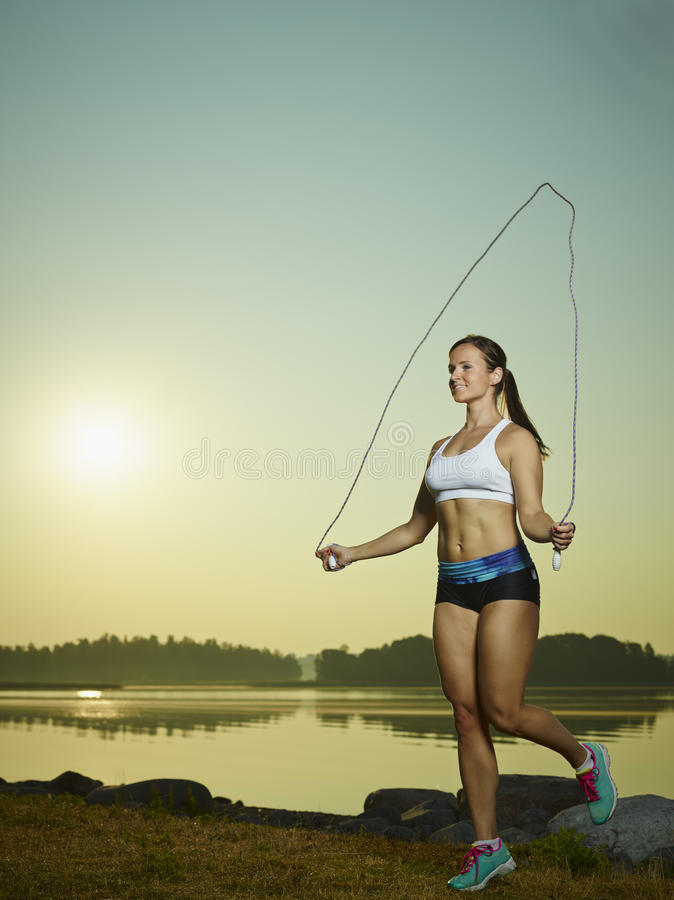 Woman and skipping rope. Young fitness woman used a skipping rope, sun and sea on background, copy space stock photo