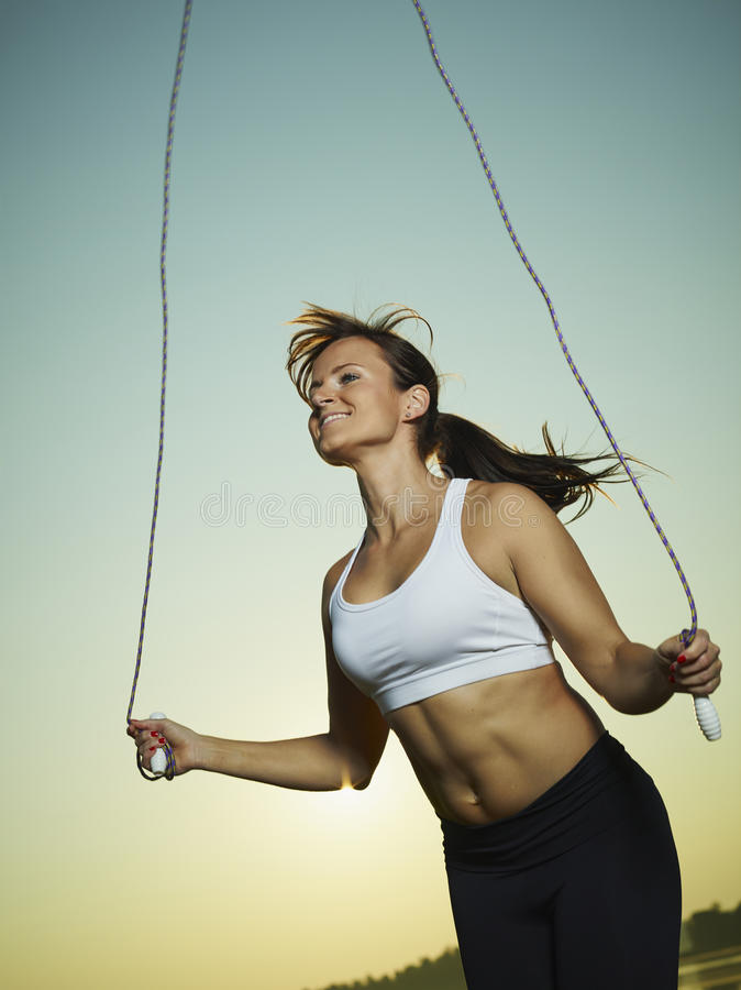 Woman and skipping rope. Young fitness woman used a skipping rope, sun and sky on background royalty free stock images
