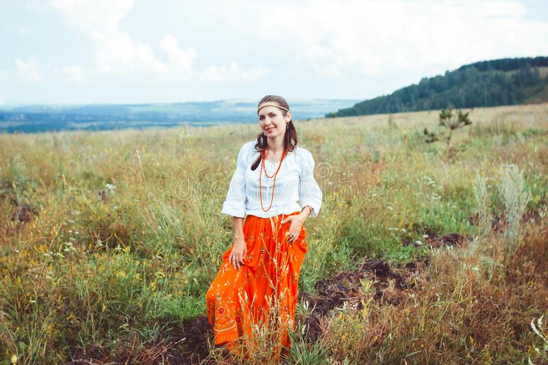 Woman in a skirt in the field. Portrait of a young girl in a red skirt in the field royalty free stock image