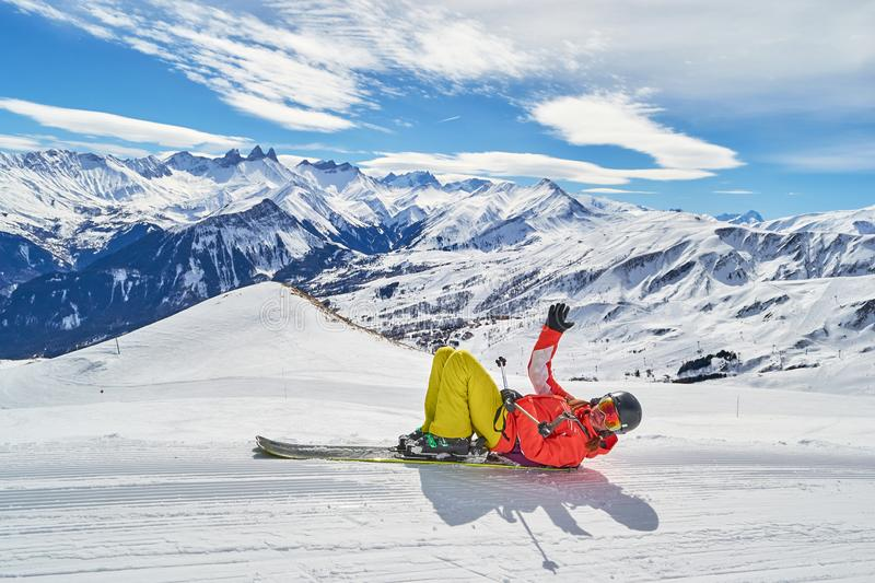 Woman on skis posing at Les Sybelles ski domain, on a blue sky sunny day, with Aguilles d Arves peak in the back. Woman on skis posing at Les Sybelles ski stock photography