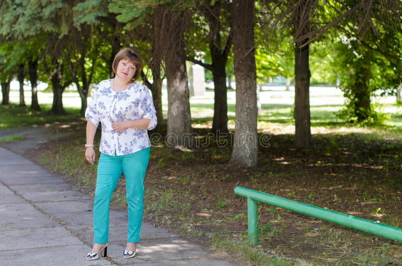 A woman of Slavic appearance with a cherubic plan in nature. A woman of Slavic appearance strolls through the park royalty free stock photo