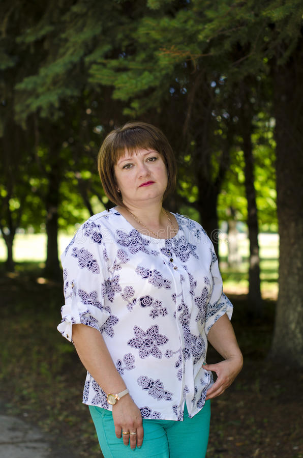 A woman of Slavic appearance poses against the background of park. A woman of Slavic appearance with a cherubic plan in nature royalty free stock images