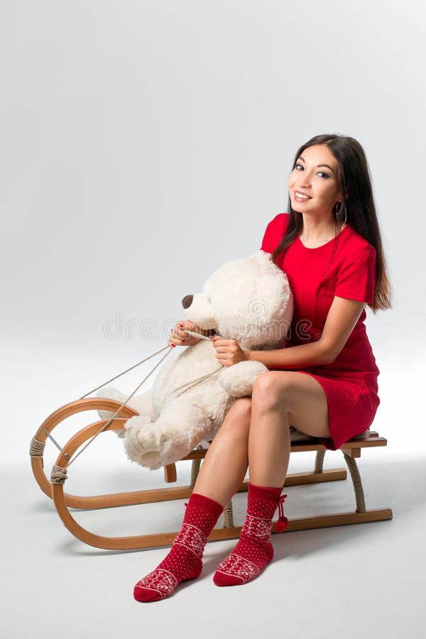 Woman on sledge with toy bear on white. Young woman on sledge with toy bear on white background stock photo