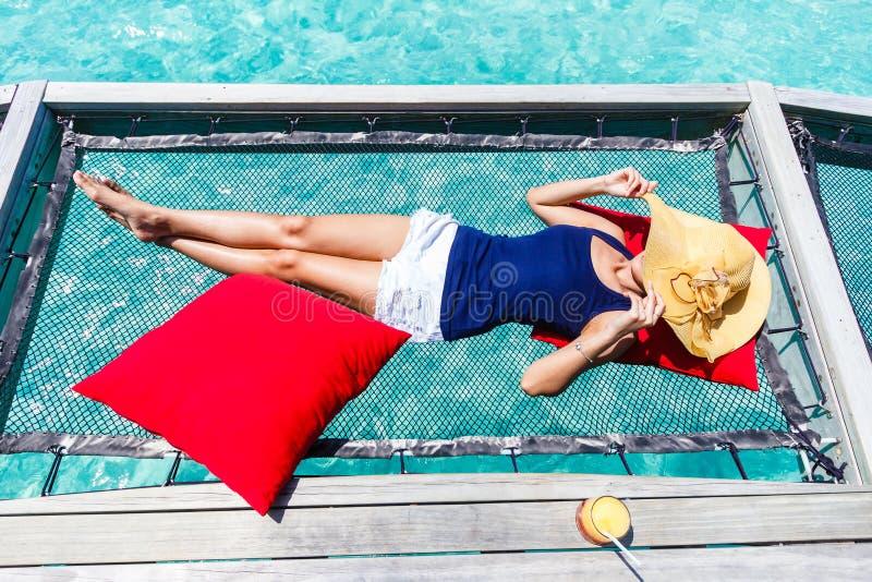 Woman sleep on net over sea. royalty free stock image
