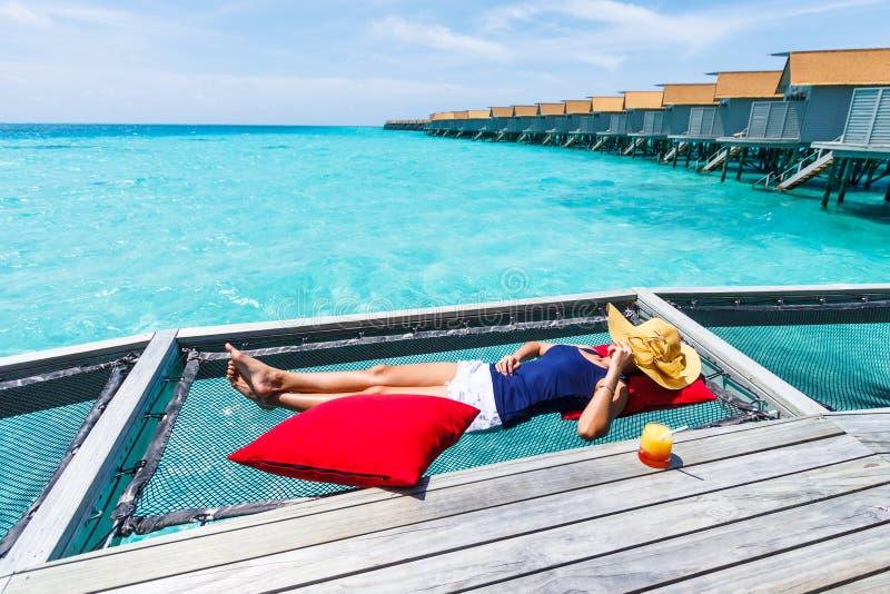 Woman sleep on net over sea. royalty free stock images
