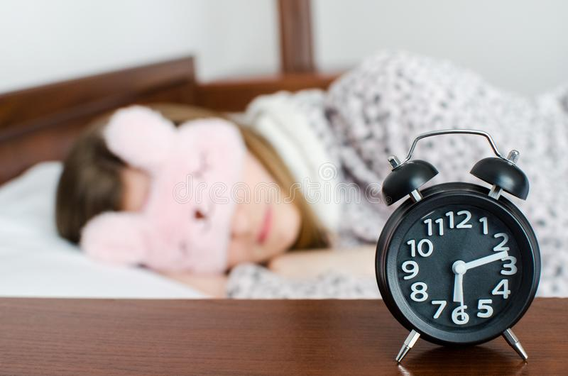 Woman sleeping with alarm clock stock photography