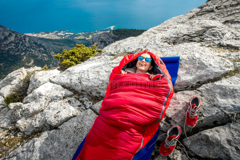 Woman in sleeping bag on the mountain. Young woman lying in red sleeping bag on the rocky mountain stock photography