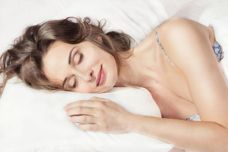 Woman sleeping in the bed. Closeup portrait of a young beautiful woman sleeping on the bed. Sweet dreams. Good night stock photo