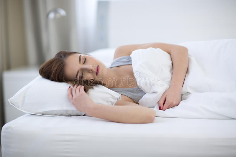 Woman sleeping on the bed at home stock photography