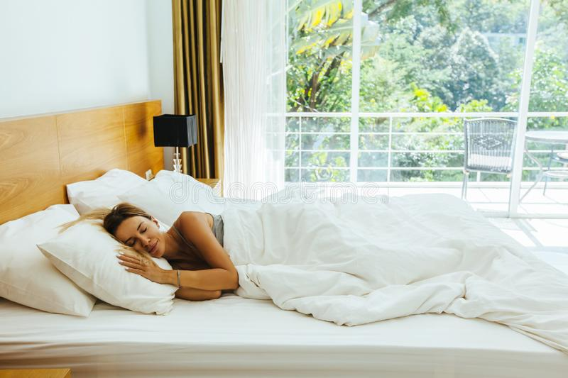Woman sleeping on bed in hotel room. Woman sleeping on bed in luxury hotel room in the morning infront of big window. Chilling well on comfy matress and pillows royalty free stock photo