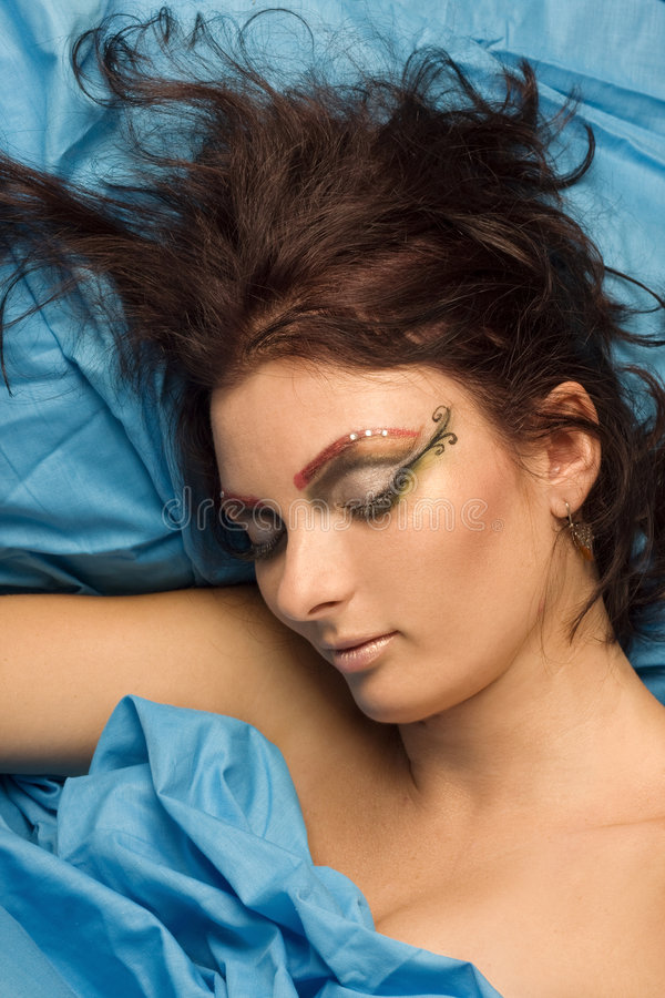 Woman sleeping in blue bedclothes. Woman sleeping blue studio lighting makeup eyes closed dreams bedclothes royalty free stock images