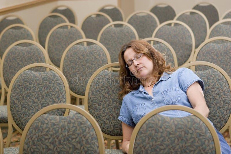 Woman sleeping at boring conference royalty free stock photos