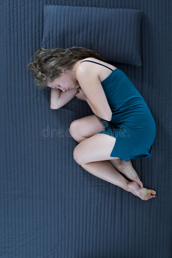 Woman sleeping curled up. Sad woman sleeping curled up at night stock images