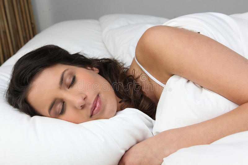 Woman sleeping peacefully. Comfortably in bed stock image