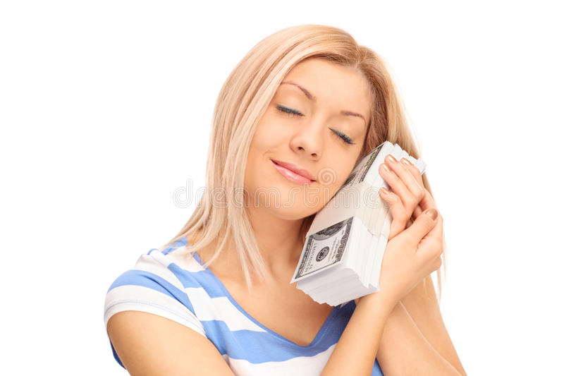 Woman sleeping on a stack of dollar bills royalty free stock image