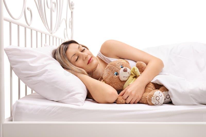 Woman sleeping with a teddy bear stock photos