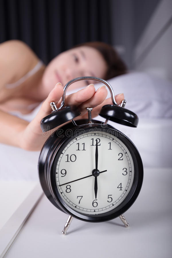 Woman sleeping and wake up to turn off the alarm clock in morning. Woman sleeping and wake up to turn off the alarm clock in the morning stock photography