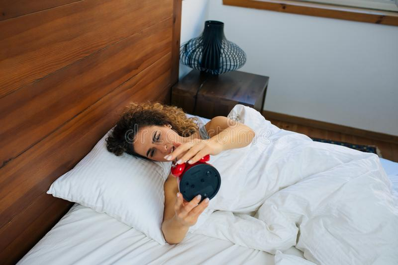 Woman sleeping and wake up to turn off the alarm clock in the morning. Beautiful woman awakened by alarm clock in the bed at morning time. A woman is unhappy stock photos