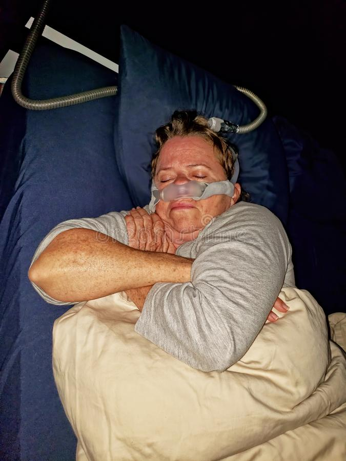 Woman sleeping while wearing CPAP device. Courtesy Wikipedia: Continuous positive airway pressure CPAP is a form of positive airway pressure ventilator, which royalty free stock photo