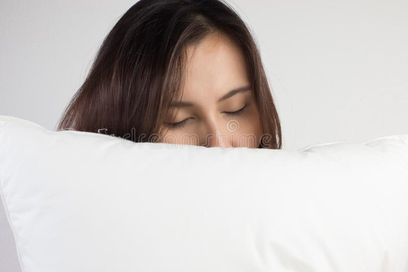 Woman sleeping well in bed hugging soft white pillow royalty free stock photo