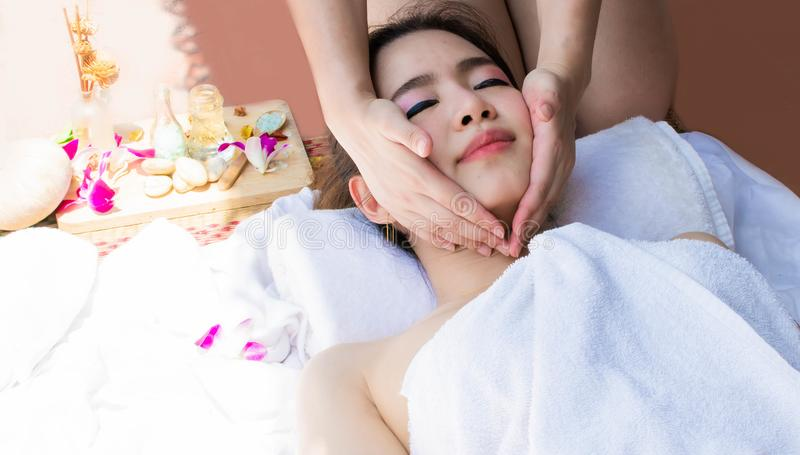 Woman is sleeping well on comfortable bed while getting face massage stock images