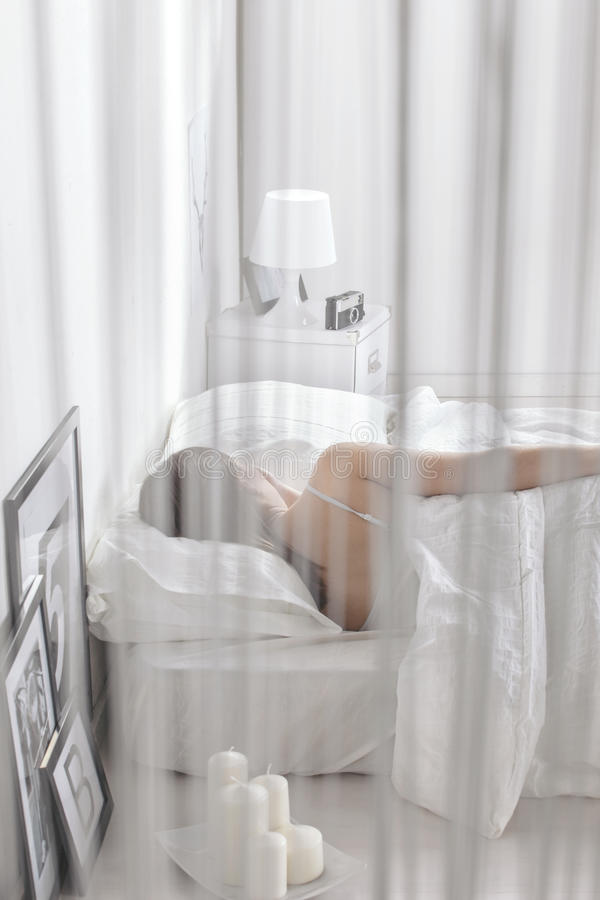 Woman sleeping in a white bed. Relaxing at home. Woman resting on bedroom stock photography