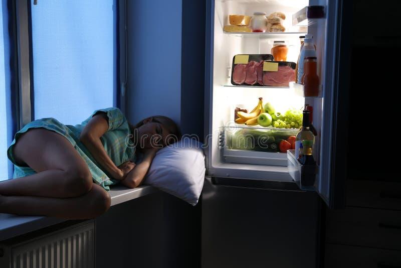 Woman sleeping on window sill near open refrigerator in kitchen stock image