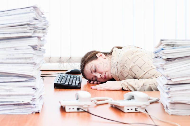 Woman sleeping on working place. Caucasian woman sleeping on working place in office room stock photo