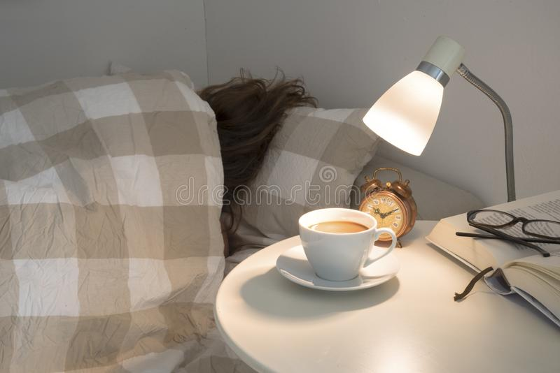 Woman sleeps turned away in bed and doesn`t want to get up, the royalty free stock photo