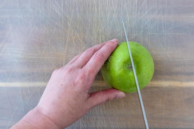 Woman slicing a green Granny Smith apple on a well-used plastic cutting sheet over a wood cutting board, hands and chefs knife stock photos