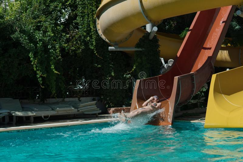 Woman slides down from the slide into the pool. Unknown woman slides down from the slide into the pool in an outdoor water park while relaxing on sunny summer stock image