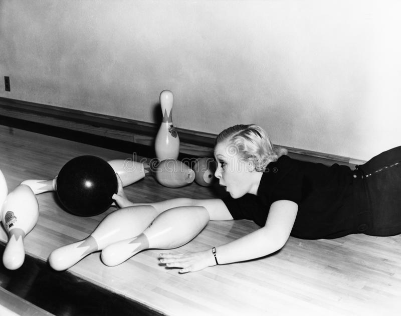 Woman sliding down bowling alley with ball royalty free stock photography