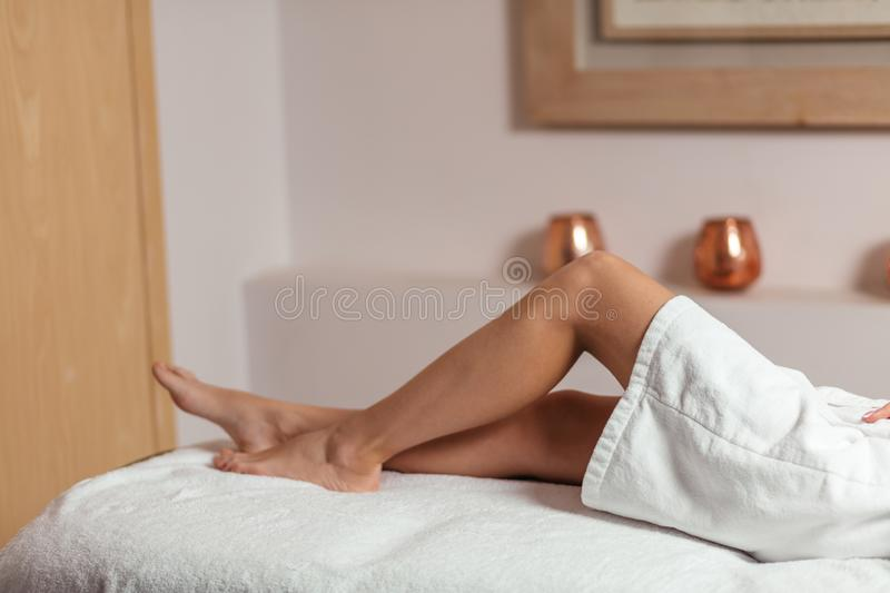 Woman with slim healthy legs sitting on bed at home. Close up side view photo.wellness, wellbeing royalty free stock images