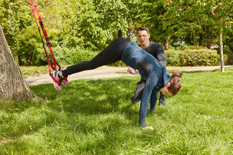 Woman sling training with fitness trainer stock photography